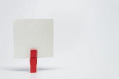 Morceau de papier de note maintenu par l'agrafe en bois rouge avec le fond blanc et le foyer sélectif Photo stock