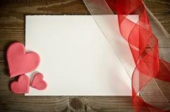 Morceau de papier se trouvant avec des coeurs et des rubans Images libres de droits