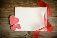 Morceau de papier se trouvant avec des coeurs et des rubans Photos libres de droits