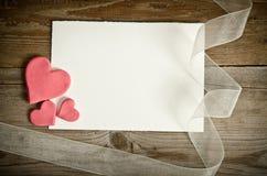 Morceau de papier se trouvant avec les coeurs et le ruban Photos libres de droits