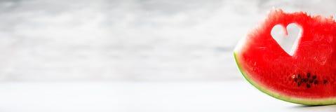 Morceau de pastèque avec la forme de coeur sur le fond concret gris Copiez l'espace Configuration plate Carte de voeux, concept d Images libres de droits