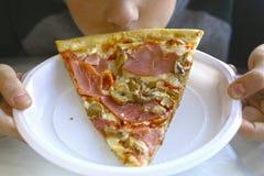 Morceau de pizza dans des mains humaines Photo libre de droits