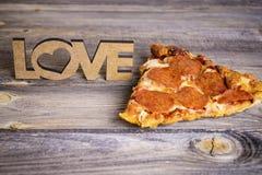 Morceau de pizza sur un vieux fond en bois Photo stock