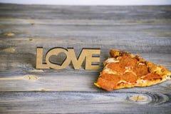 Morceau de pizza sur un vieux fond en bois Photographie stock libre de droits