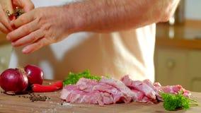 Morceau de porc frotté avec les mains masculines de sel sur un conseil en bois Clip vidéo de HD L'homme répand avec le poivre par banque de vidéos