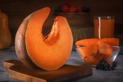 Morceau de potiron frais sur un conseil en bois dans la perspective des carottes coupées, d'un verre de jus et d'un panier en osi image libre de droits