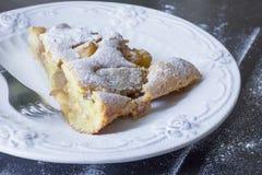 morceau de tarte aux pommes d'un plat blanc élégant Fond en bois noir Photos stock