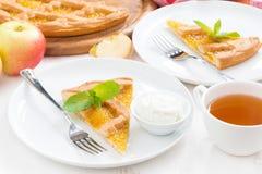 Morceau de tarte aux pommes fraîche avec de la crème et la tasse fouettées de thé Photographie stock libre de droits