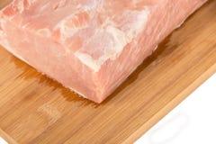 Morceau de viande cru sur un conseil en bois sur un fond blanc Photos stock