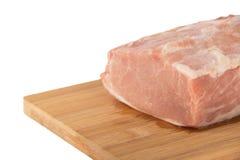 Morceau de viande cru sur un conseil en bois sur un fond blanc Images stock