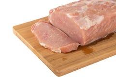 Morceau de viande cru sur un conseil en bois sur un fond blanc Photos libres de droits