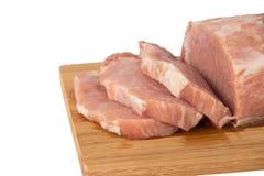 Morceau de viande cru sur un conseil en bois sur un fond blanc Photo stock