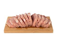 Morceau de viande cru sur un conseil en bois sur un fond blanc Photographie stock