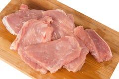 Morceau de viande cru sur un conseil en bois sur un fond blanc Images libres de droits