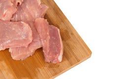 Morceau de viande cru sur un conseil en bois sur un fond blanc Photo libre de droits