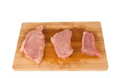 Morceau de viande cru sur un conseil en bois sur un fond blanc Photographie stock libre de droits