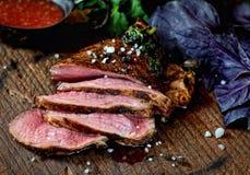 Morceau de viande grillé juteux sur une planche à découper, basilic, persil, épices sur un fond en bois foncé Photographie stock libre de droits