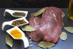 Morceau de viande prêt à préparer, avec leurs espèces et feuilles respectives de baie photos stock