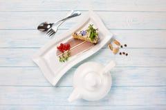 Morceau du gâteau, thé dans une théière sur les conseils bleus images stock