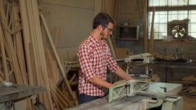Morceau en bois de meulage de jeune charpentier masculin à son atelier clips vidéos