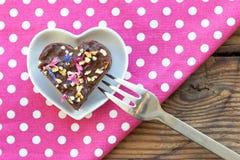 Morceau en forme de coeur mignon de gâteau de chocolat arrosé avec des fleurs Photos libres de droits