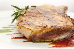 Morceau juteux de côtelette de porc frite avec la sauce de romarin et tomate photos libres de droits