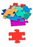 Morceau rouge près de la pile des puzzles denteux Image libre de droits