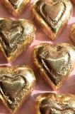 Morceau sous emballage souple de chocolat de forme de coeur d'or Images stock