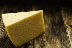 Morceau triangulaire de fromage sur une surface en bois images stock