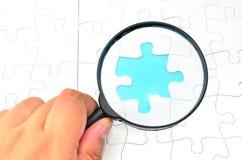 Morceaux ÉTROITS de -puzzle avec une loupe Photographie stock libre de droits