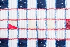 Morceaux carrés de tissus colorés, cousus par les coutures rouges et bleues de zigzag sur le tissu de blanc de soulagement Images libres de droits