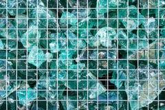 Morceaux cassés de turquoise de verre derrière le gril en aluminium Texture, fond photos stock