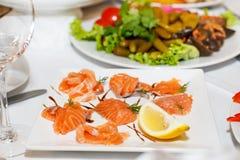 Morceaux découpés en tranches de saumons et de citron d'un plat blanc Image libre de droits