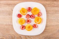 Morceaux d'abricots et de merises dans le plat blanc Images libres de droits