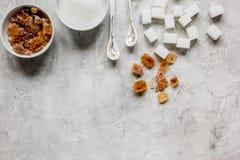 Morceaux de blanc et de sucre roux sur la moquerie grise de vue supérieure de fond de table  Photographie stock libre de droits
