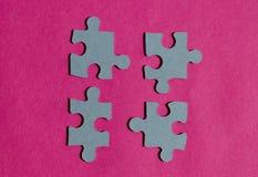 Morceaux de casse-tête sur le fond rose lumineux Images stock