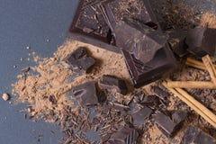 Morceaux de chocolat amer, poudre de cacao et cannelle cassés foncés Fond de chocolat Image stock