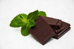 Morceaux de chocolat avec une feuille de menthe Photographie stock libre de droits