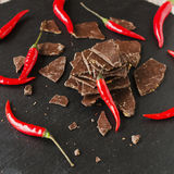 Morceaux de chocolat foncé avec des piments sur le Coal Board noir Image stock