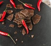 Morceaux de chocolat foncé avec des piments sur le Coal Board noir Photo libre de droits