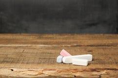 Morceaux de craie sur un fond et un tableau en bois Photos stock