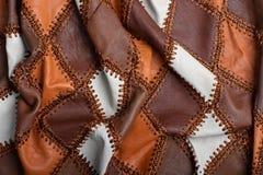 Morceaux de cuir multicolore cousus avec le fil, tissu bosselé images libres de droits