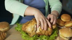 Morceaux de femme de poids excessif de viande violents outre de poulet rôti, les mangeant avidement banque de vidéos