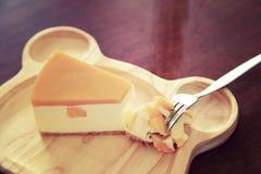 Morceaux de gâteau au fromage de mangue de plat en bois Images stock