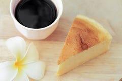 Morceaux de gâteau au fromage de style japonais et de tasse de café noir de plat en bois Images libres de droits