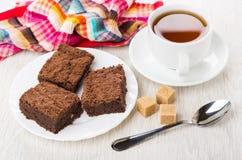 Morceaux de gâteau de chocolat dans le plat, sucre, tasse de thé Photographie stock