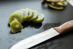 Morceaux de kiwi sur un fond noir, fruit texturisé et tropical, consommation saine, Photographie stock libre de droits