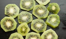 Morceaux de kiwi sur un fond noir, fruit texturisé et tropical, consommation saine, Images libres de droits