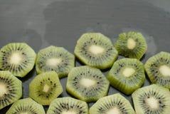 Morceaux de kiwi sur un fond noir, fruit texturisé et tropical, consommation saine, Images stock