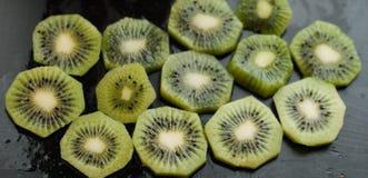 Morceaux de kiwi sur un fond noir, fruit texturisé et tropical, consommation saine, Image libre de droits